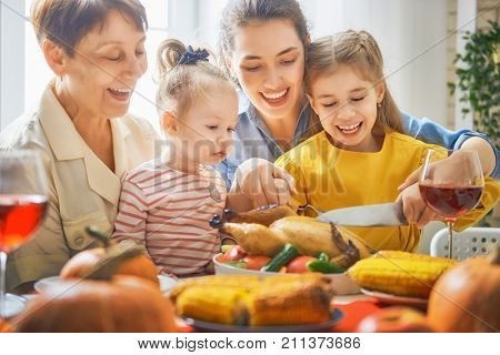Happy Thanksgiving Day! Autumn feast. Family sitting at the table and celebrating holiday. Traditional dinner. Grandmother, mother and daughter. poster