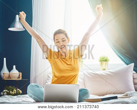 Happy casual beautiful woman working on a laptop sitting on the bed in the house.