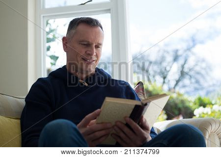Smiling man reading novel on sofa in living room at home