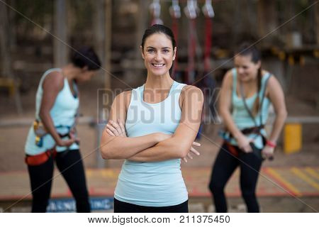 Portrait of beautiful woman standing with arms crossed in park