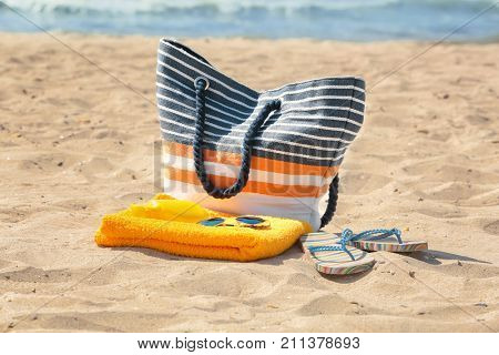 Beach towel with sunglasses and bag on sand