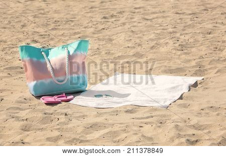 White beach towel with sunglasses and bag on sand