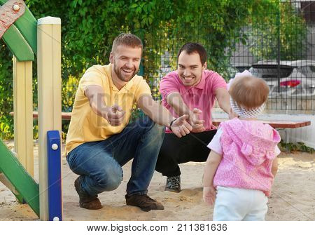 Male gay couple with adopted baby girl, outdoors