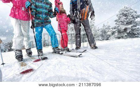 Skiing, winter fun concept- Skiing family enjoying winter vacation on snow