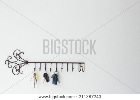 Various keys hanging on hook against white wall