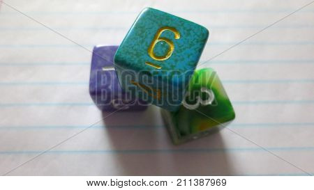 three brightly colored six sided dice as used for board games or roleplaying tabletop games stacked on lined notebook paper