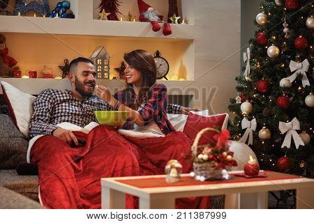 Girl feeding boyfriend with popcorn in bed while watching movie for Chrismas eve