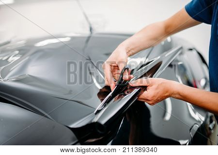 Male specialist with scissors, car tinting film poster