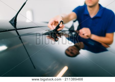 Worker with scissors, car tinting installation