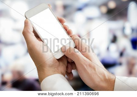 Businessman holding blank screen smartphone in office
