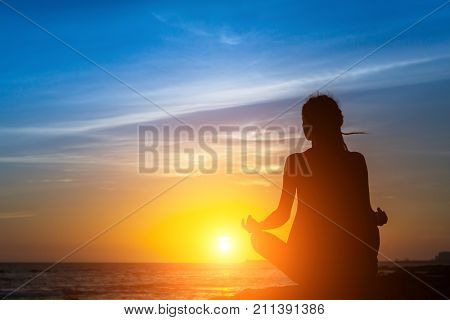 Yoga woman silhouette meditation at the sea beach during amazing sunset.