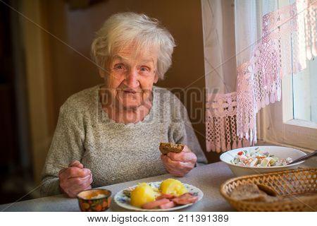 An elderly woman eats at home.