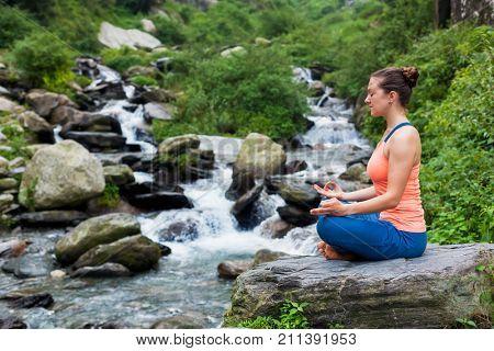 Woman meditating in Hatha yoga asana Padmasana outdoors at tropical waterfall