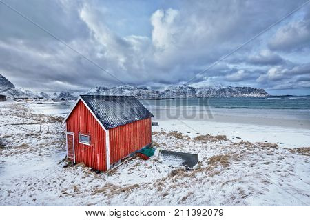 High Dynamic Range (HDR)  image of red rorbu house shed on beach of fjord. Skagsanden beach, Lofoten islands, Norway