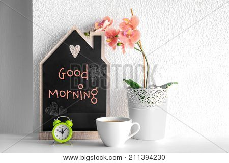 Cup of aromatic coffee, small blackboard with text GOOD MORNING and flower on table