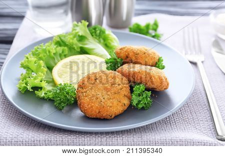 Plate with delicious salmon patties on table