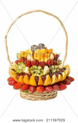 Gift basket with fruits and sweets. Basket with fruits and berries in chocolate isolated on white background. Handmade. Strawberries and grapes, citrus, apple and kiwi.