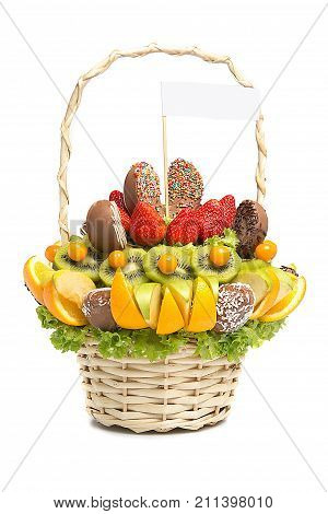 Gift basket with fruits and sweets. Basket with fruits and berries in chocolate isolated on white background. Handmade. Strawberries and citrus, apple, kiwi.