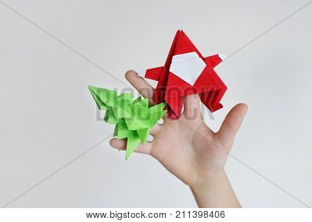 Lesson of origami. Santa Claus of origami a fir-tree of origami from paper on palm fingers
