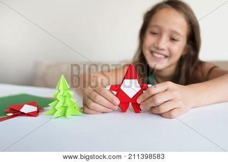 Lesson of origami. The child puts Santa Claus origami and a fir-tree of origami from paper.