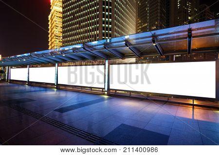 blank propaganda poster by sidewalk in midtown of shanghai at night