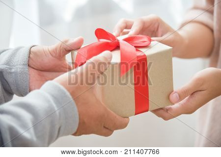 Closeup on hands Asian woman giving a brown gift box to elderly man for Birthday Christmas and New year on white background.