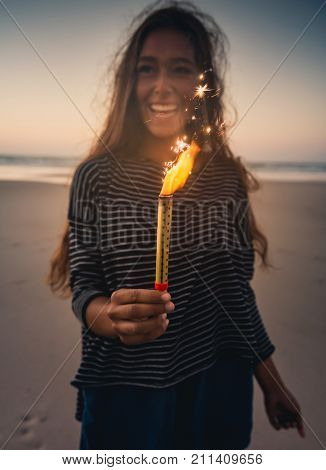 Teenage girl on the beach holding Fireworks