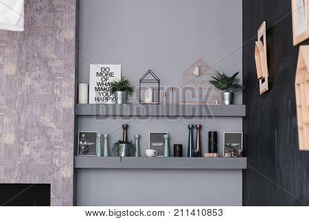 contemporary scandinavian interior with shelves full of decor objects on the grey wall.