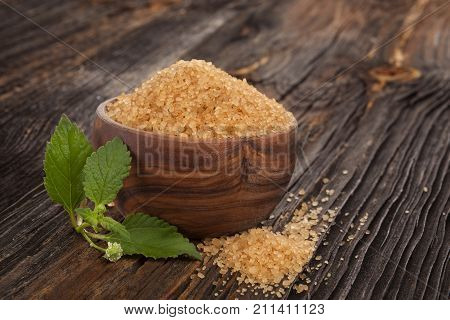 Bowl Of Brown sugar in wooden bowl and aztec sweet herb or bushy lippia honeyherb hierba dulce on wooden table.