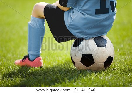 Child Sitting on Soccer Ball. Young Boy with Soccer Ball on the Pitch. Soccer Grass in the Background. Youth Sport Football Background