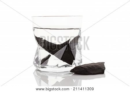Shungite stones in glass of water isolated on white background. Water purification alternative medicine.