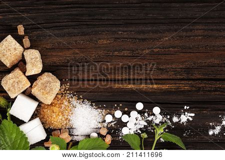 Various types of sugar - brown white crystal cane and powdered sugar and artificial sweetener from above.