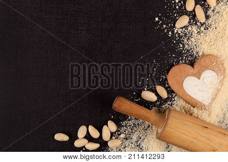 Almond flour background. Almond nuts flour wooden rollin pin and ginberbread from above. Gluten free flour.