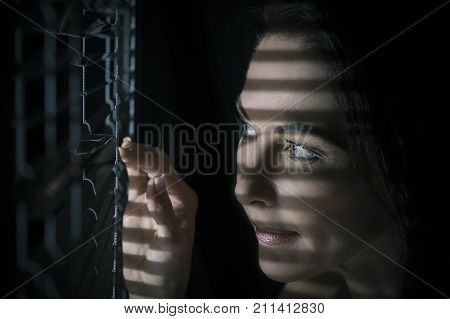 Portrait of a woman standing in the dark looking through blinds artistic conversion