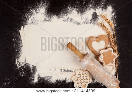 Christmas baking background. Rolling pin gingerbread flour on black table from above. Creative festive background.