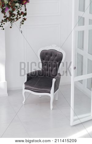 Black and white velours vintage armchair in minimalistic scandinavian room. vertical photo with clear space for text.