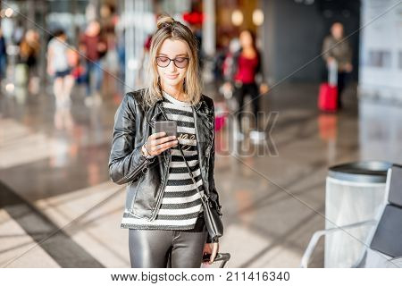 Young business woman dressed casually walking with phone at the departure hall of the airport waiting for the flight