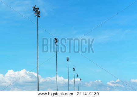 The vast bright blue sky and coulds with airport spotlight pylon nature background.
