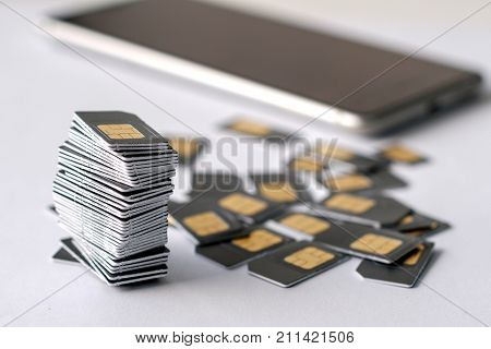 the phone in the background in the foreground a stack of assembled SIM card is gray, many SIM cards