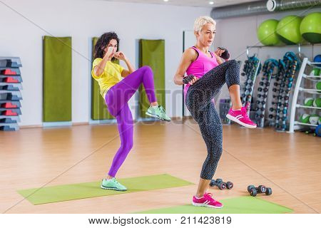 Two fit women doing straight leg kicking exercise while working-out in gym.