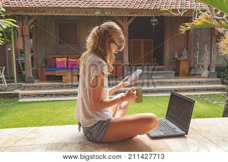 Girl holding cellphone coffe mug with laptop in the garden porch.