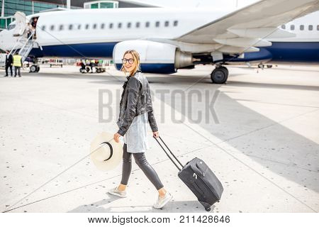Young woman in leather jacket walking with suitcase near the airplane outdoors on the airport runway