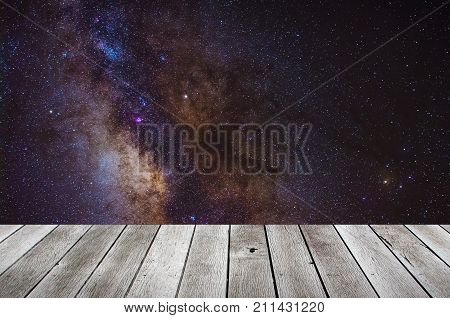 wooden terrace or desk with copy space for display of product or object presentation with milky way galaxy long exposure photograph background