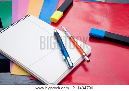 Different stationary. Pen pencil markers paper notepad laying on red blue yellow pink green plastic folders