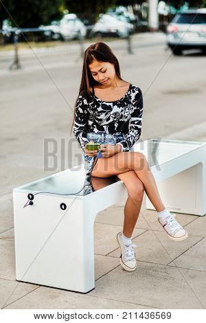 Beautiful woman charging her phone on free multipurpose solar panel charger incorporated in to sitting bench for cittisents.Modern technology free energy for everyone .