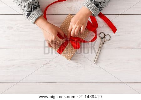 DIY hobby. Woman's hands wrapping christmas or other holiday handmade present in paper with red ribbon. Making bow at present box, decoration of gift. Scissors on white wooden table, top view.