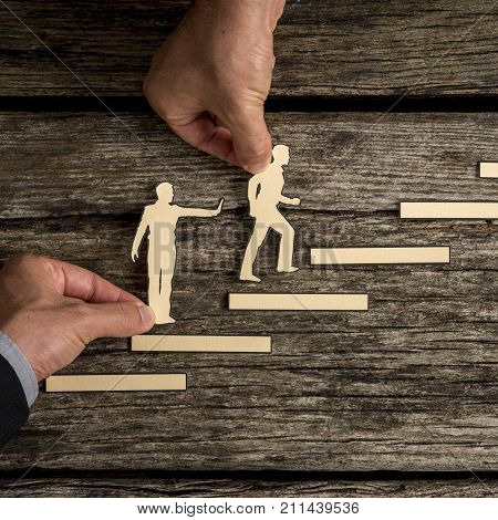 Business Teamwork Concept With The Hands Of Two Businesspeople Supporting Paper Cut Outs
