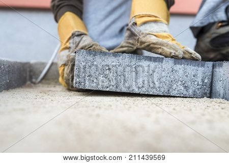 Building contractor laying a paving slab or brick placing it on the sand foundation with gloved hands in a low angle view.