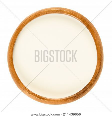Fresh sweet cream in wooden bowl, a dairy product composed of the higher butterfat layer skimmed from the top of milk before homogenization. Macro food photo close up from above on white background.