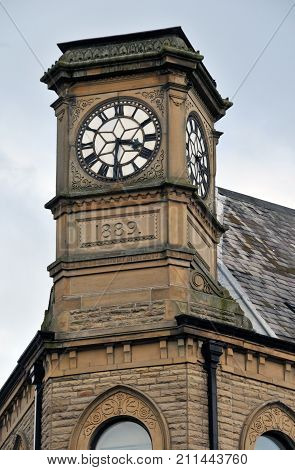 old clock on a stone tower in hebden bridge west yorkshire